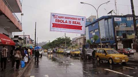 People hang out in a street under a banner which warns people to be cautious about Ebola, in Monrovia, Liberia. (Source: AP)
