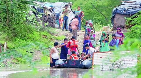 Fire officials rescued around 25 people, including women and children, who were stranded due to flooding at Devipura in Vadodara, on Saturday. (Source: Express photo by Bhupendra Rana)