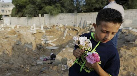 Palestinian Saeb Afana, 12, stands on the edge of a large crater from an Israeli missile strike that destroyed several graves, as he carries flowers at a cemetery in Gaza City. Monday marked the beginning of the three-day Eid al-Fitr holiday, which caps the Muslim fasting month of Ramadan. (Source: AP)