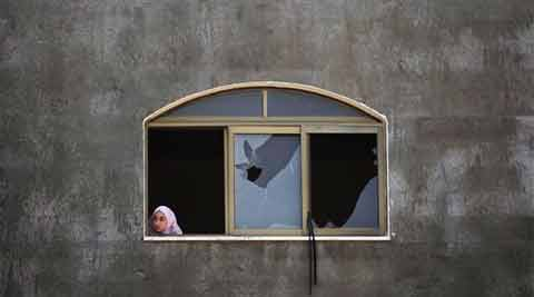 A Palestinian girl looks at a damaged home after it was hit by an Israeli missile strike in Gaza City. (Source: AP)