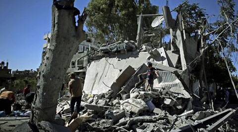 A Palestinian child retrieves a stuffed animal from a destroyed building following an Israeli missile strike in Gaza Strip on Friday, July 11, 2014. (Source: AP)