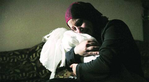 A woman holds the body of her one-year-old daughter who medics said died Friday from injuries in an Israeli air strike. (Source: AP)