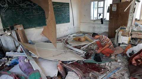 A Palestinian collects body parts in a classroom at the Abu Hussein UN school in Jebaliya refugee camp, northern Gaza Strip, hit by an Israeli strike on Wednesday. (Source: AP)