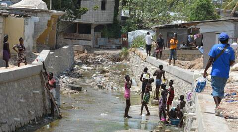 Residents of the Delmas section of Port-au-Prince wash in one of the trash-clogged, stagnant canals that criss-cross the Haitian capital and are a breeding ground for the newly arrived Chikungunya mosquito-borne virus. (Source: AP)