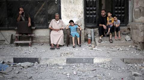 Neighbors of Palestinian Hamas leader, Mahmoud Zahar, sit outside their homes following an early morning Israeli missile strike that destroyed Zahar's house in Gaza City. (Source: AP)