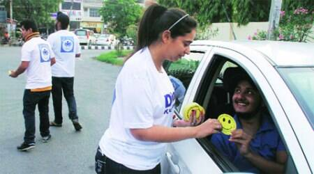 NGO members distribute smileys to commuters in Ludhiana on Tuesday.  	Gurmeet Singh