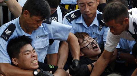 Protesters are taken away by police officers after hundreds of protesters staged a peaceful sit-ins overnight on a street in the financial district in Hong Kong. (Source: AP)