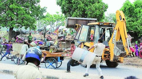 Policemen lathicharge residents of Mansa Devi Complex after they hurled stones at the police following HUDA's anti-encroachment drive.