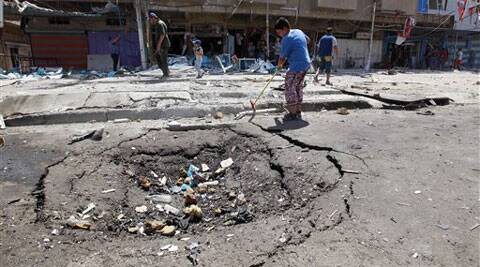Civilians inspect the site of a bomb attack in the Jihad neighborhood in Baghdad, Saturday, July 19, 2014. (Source: AP)