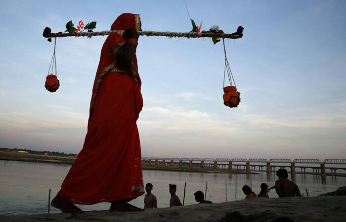 A Kanwaria woman carries canisters filled with holy water from the Ganga River in Allahabad. (Source: AP)