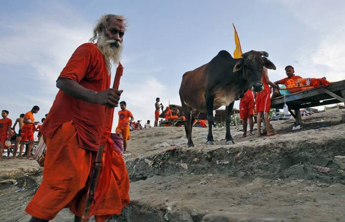 A Kanwaria walks on the banks of the River Gangas as others rest in Allahabad. (Source: AP)<br />Kanwarias are devotees performing a ritual pilgrimage in which they walk the roads of India, clad in saffron, and carrying ornately decorated canisters of sacred water from the Ganga River over their shoulders to take it back to Hindu temples in their hometown, during the month of Shravana.