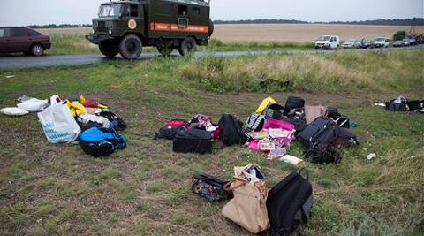 Passengers' personal luggage is collected at the site of a crashed Malaysia Airlines passenger plane near the village of Rozsypne, Ukraine, eastern Ukraine Friday, (Source: AP)