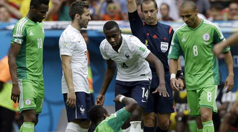 Referee shows a yellow card to Blasie Matuidi (centre) after he fouled Nigeria's (Source: AP)