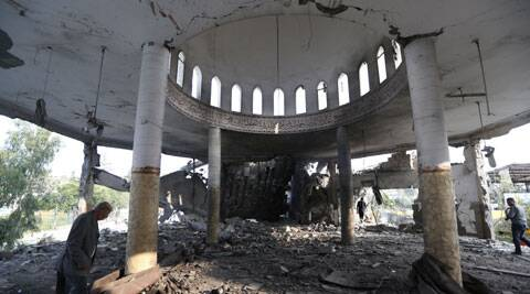 Khaled Sharmi, 67, left, walks inside the Al Aqsa Martyrs mosque destroyed by an overnight Israeli strike, in Gaza City. (Source: AP)