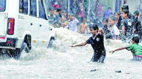 Children play in a waterlogged road during rain in Vadodara on Tuesday. (Express photo by Bhupendra Rana)