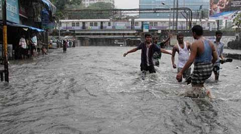 People wade through water logged streets as the city experienced heavy shower of rain in Mumbai. (Source: PTI)