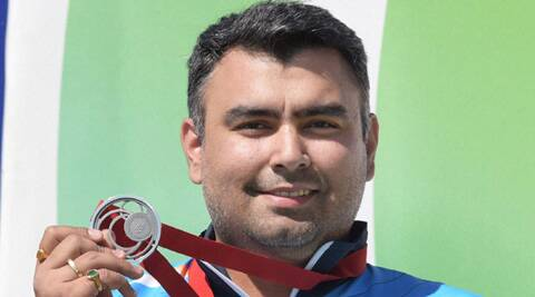 India's Gagan Narang flaunts his silver medal on the podium after winning the 50m rifle prone. (Source: AP)