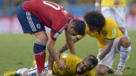 Colombia's James Rodriguez and Brazil's Marcelo attend to Neymar who grimaces in pain after being kneed. (Source: AP)