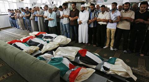 Palestinians pray at a mosque in front of the national flag-draped bodies of five members of the al-Halaq immediate and extended family, killed Sunday by an Israeli strike at their house in Gaza City. (Source: AP)
