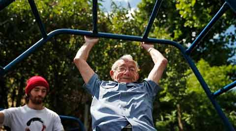 George Jackson, 85, an army veteran and former boxer swings on monkey bars as he participates at a parkour class for elderly people at a park in south London. (Source: AP)