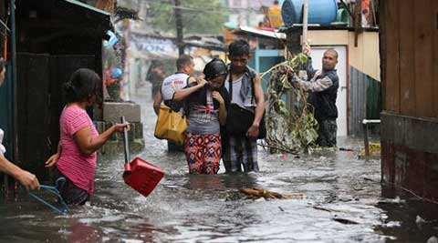 Residents wade through floods as they go back to their home while Typhoon Rammasun batters suburban Quezon city, north of Manila, Philippines. (Source: AP)