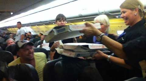 Passengers being given pizzas by the crew of the plane. (Source: Twitter)