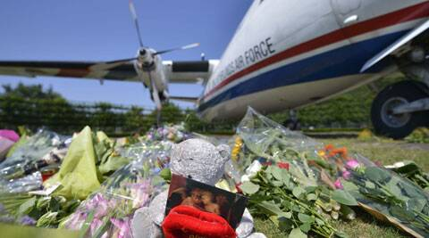 Flowers and a teddy bear are placed in front of a plane prior a ceremony to mark the return of the first bodies of passengers and crew killed in the downing of Malaysian flight MH17. (Source: AP)