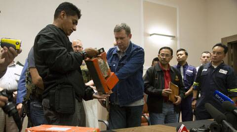 A Malaysian investigator, left, takes a black box from Malaysia Airlines Flight 17 as it <span class=