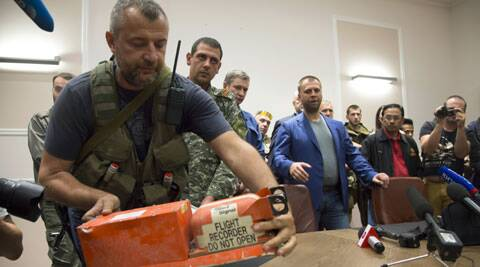 A pro-Russian fighter places a black box from the crashed Malaysia Airlines Flight 17 on a table while handing it over from Donetsk People's Republic officials to Malaysian representatives in the city of Donetsk, eastern Ukraine. (Source: AP)