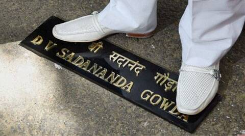 Congress ex MLA Mukesh Sharma stands on the name-plate of Railway Minister DV Sadananda Gowda during a protest against the Rail Budget, outside Gowda's residence (Source: AP)
