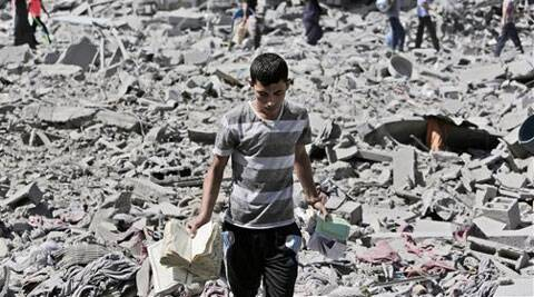 Palestinian Mahmoud Elbiss, 19, holds copies of the Holy Quran, Islam's holy book, that he salvaged from the rubble of houses, destroyed by Israeli strikes in Beit Hanoun, northern Gaza Strip, Saturday, July 26, 2014. (Source: AP)