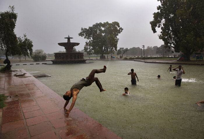 A youth dives into water as it rains in New Delhi on Wednesday.<br /> According to the weather office, the monsoon rains are expected to arrive at the national capital in a couple of days. (Source: AP)