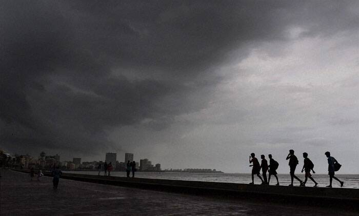 Heavy rains on Wednesday lashed the metropolis, severely disrupting road, rail and suburban train services and inconveniencing lakhs of commuters and office goers. <br /> People enjoy at the Marine Drive as it rains in Mumbai on Wednesday. (Source: PTI)