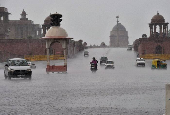 Vehicles move at Vijay Chowk during rains in New Delhi. (Source: PTI)