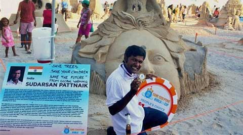 Sand artist Sudarsan Pattnaik poses with his award after winning the People's Choice prize for his sand sculpture of 'Save Tree, Save the Future' at World Cup of Sand Sculpting 2014 in solo category at Atlantic City USA on Saturday. (PTI Photo)