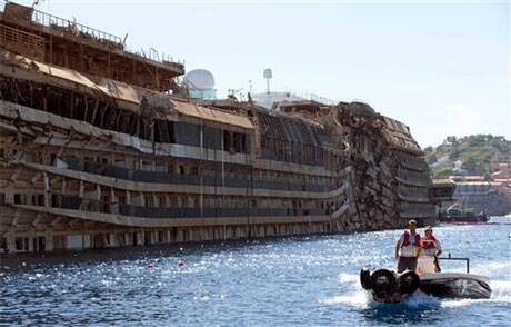 A small boat passes next to the damaged side of he Costa Concordia on the Tuscan Island of Giglio, Italy. ( File photo, Source: AP )