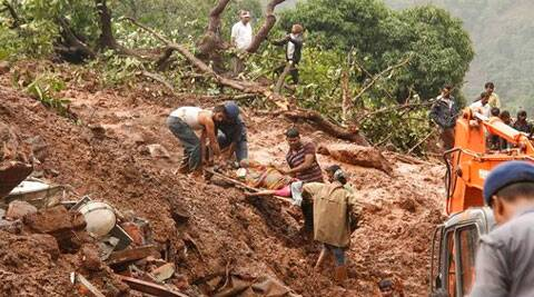 Rescue workers carry the body of a victim at the site of a landslide in Malin village. (Source: AP photo)
