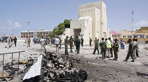 Somali soldiers stand near the wreckage of a suicide car bomb near the Somali parliament in Mogadishu, Somalia. (Source: AP