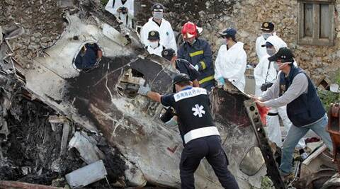 A forensic team recovers human remains among the wreckage of crashed TransAsia Airways flight GE222 on the outlying island of Penghu, Taiwan on July 24, 2014. (AP Photo)