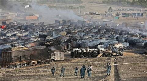 Afghan police stand guard at the site of burning oil tankers after an attack claimed by Taliban militants (Source: AP)