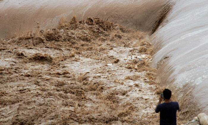 A boy captures the water currents of the raging river Tawi during flash floods on the outskirts of Jammu on Thursday. (Source: PTI)