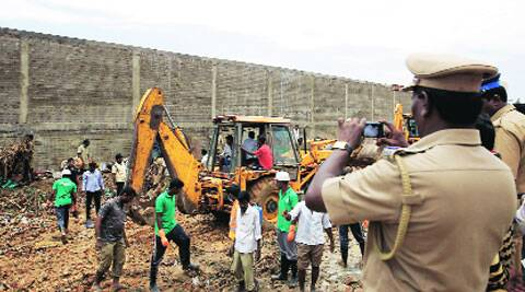 A policeman photographs the wall-collapse site as workers clear the debris on the outskirts of Chennai, Sunday.