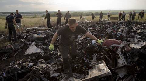 A man looks for the remains of victims in the debris at the crash site of Malaysia Airlines Flight 17 near the village of Hrabove, eastern Ukraine. (Source: AP)