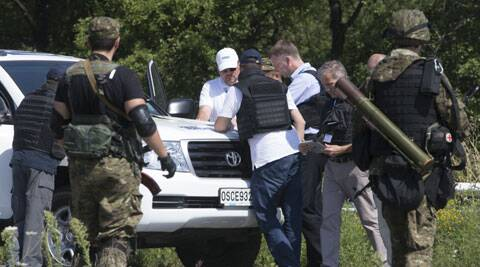 Members of the OSCE mission to Ukraine examine a map as they try to estimate security conditions outside the city of Donetsk, eastern Ukraine Wednesday, July 30, 2014. (Source: AP)