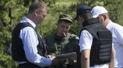 Alexander Hug, deputy head of the OSCE mission to Ukraine, left, his colleagues and a pro-Russian rebel, 2nd left, examine a map as they try to estimate security conditions outside the city of Donetsk, eastern Ukraine Wednesday, July 30, 2014. (Source: AP)