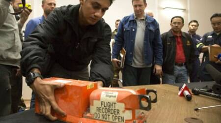 A Malaysian investigator takes a black box from Malaysia Airlines Flight 17 as it is handed over from Donetsk People's Republic officials to Malaysian representatives in the city of Donetsk, eastern Ukraine. (Source: AP)