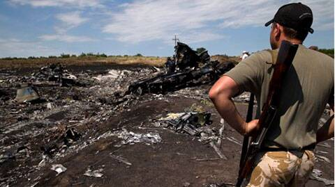 An armed man looks at charred debris at the crash site of Malaysia Airlines Flight 17 near the village of Hrabove, eastern Ukraine. (Source: AP)