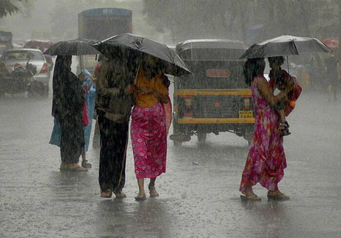 People walk on the road with umbrellas during rainfall in Mumbai. (Source: PTI)