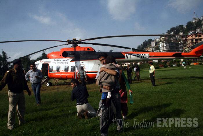 A man takes an injured son in state helicopter in Shimla. <br /> At least 23 people were on Thursday killed and another 20 injured when a private bus rolled 400 feet down into a gorge in Rohtrung village in Himachal Pradesh's Kinnaur district, 250 km from Shimla. (Source: Express photo by Lalit Kumar)