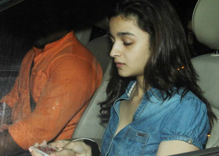 Can't do without music! Alia puts on her ear phones as she sits in her car. (Source: Varinder Chawla)